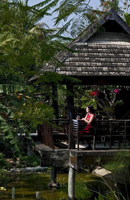 Woman in red dress in a traditional Thai House