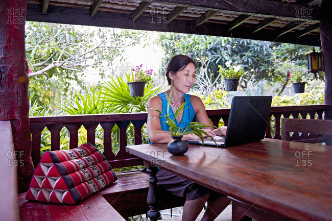 Woman working on laptop on a terrace at a traditional Thai house