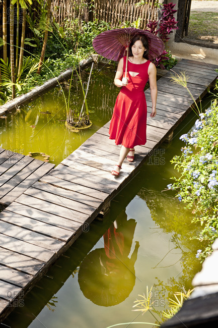 Woman in red dress walking in a Thai garden