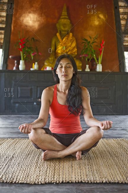 Woman meditating at traditional Thai House
