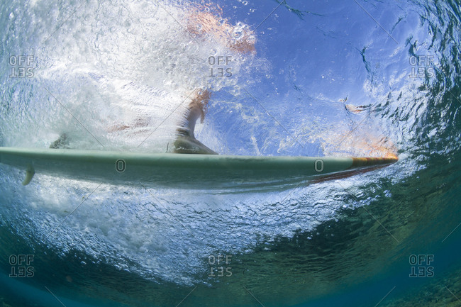 Underwater close-up of a surfer riding a wave in maldives
