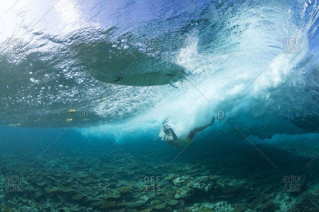 Surfers wiping out on the shallow reef in maldives
