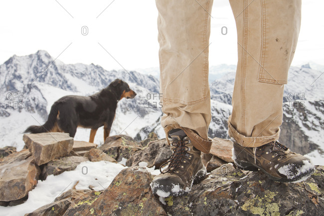A dog and the legs and boots of hiker on the summit of Frosty Mountain, British Columbia, Canada