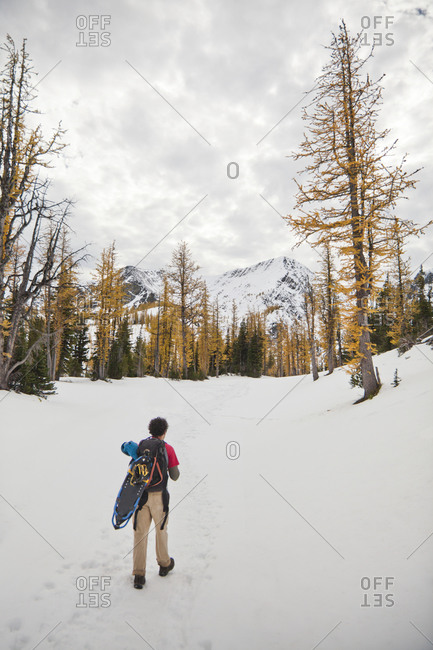 A backpacker hikes through snow toward Frosty Mountain in Manning Provincial Park, BC, Canada