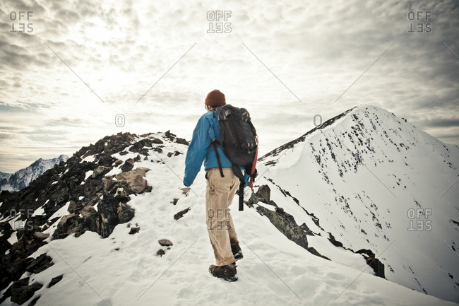 A backpacker hikes a rocky rideline toward the summit of Frosty Mountain in Manning Provincial Park, BC, Canada