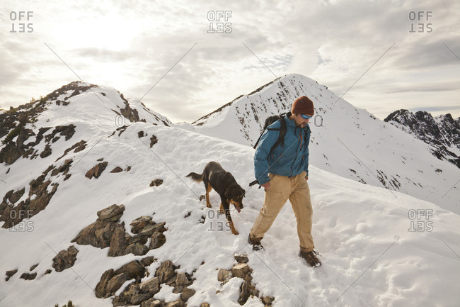 A hiker and his dog descend from  the summit of Frosty Peak in Manning Provincial Park, British Columbia, Canada