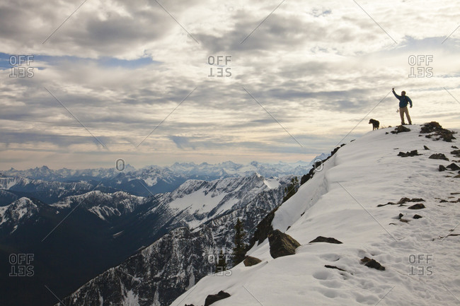 A hiker raises his fist in the air while standing on a rocky mountain ridge with his dog