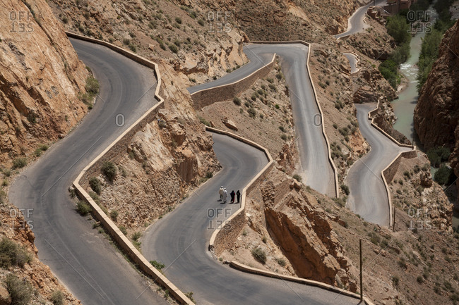 People walking on a very windy road in the Atlas Mountain, Morocco, North Africa