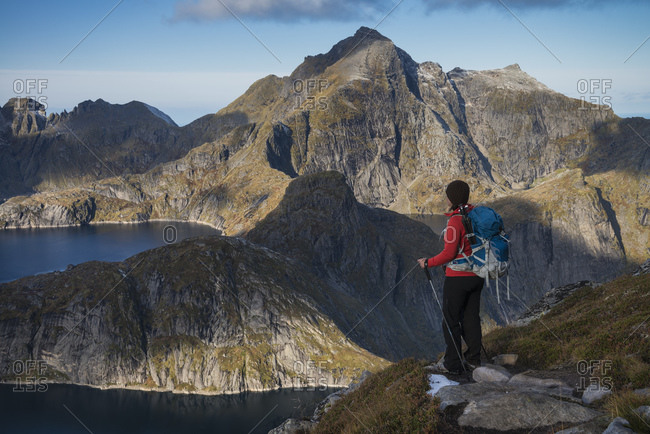 Female hiker takes in view of mountains from trail to Munken, Moskenesøy, Lofoten Islands, Norway