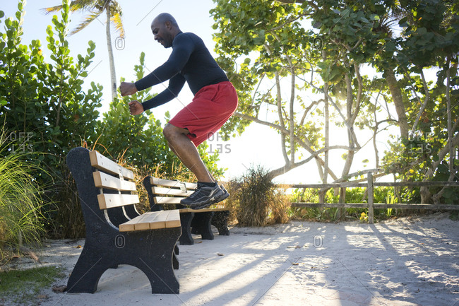 Man exercises by jumping up on a park bench in a tropical setting
