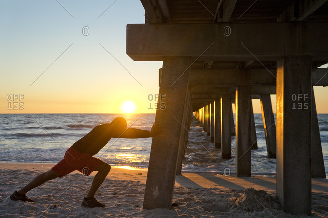 Man stretching against a pier pillar on the beach at sunset