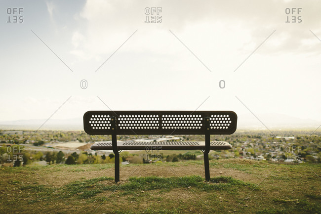 An empty bench sits over a city