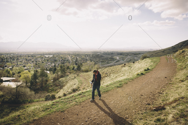 A man talks on a cell phone while walking a mountain road at sunset