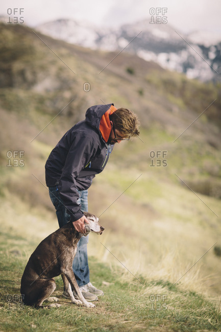 A man pets his dog on a mountain walk