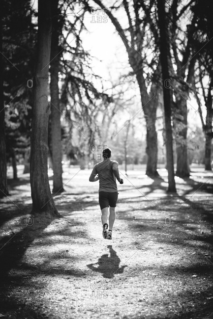 A young man jogs in a park