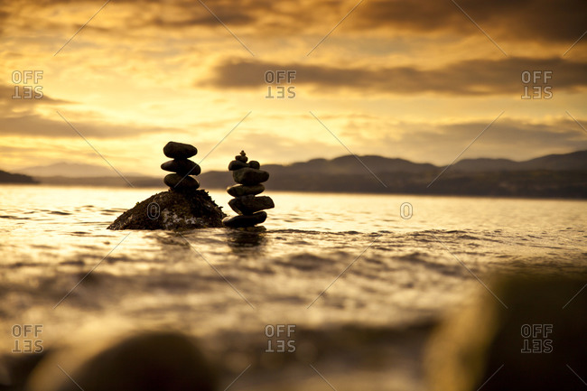 Two small rock stacks are slowly covered by water as the tide rises near Sechelt, BC, Canada