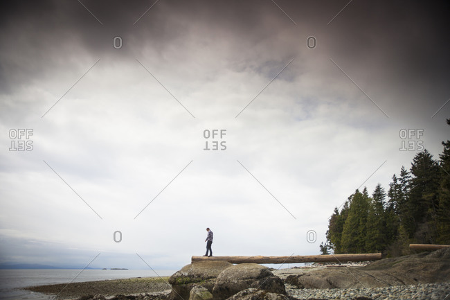 A young man balances on a log facing the Pacific Ocean at Robert's Creek Park, near Sechelt, BC, Canada