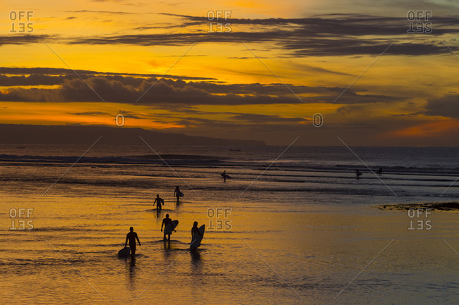 Group of surfers at sunrise