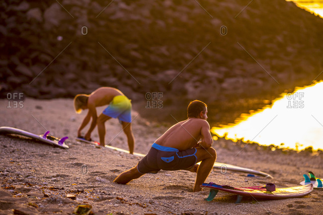 Surfers stretching on the beach before surfing