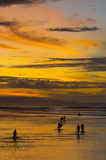 Surfers heading out at sunrise