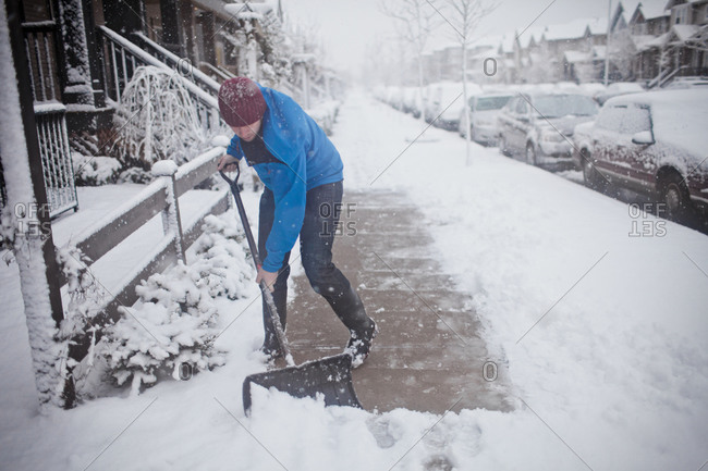 A man shovels the sidewalk outside of his suburban house during a snow storm