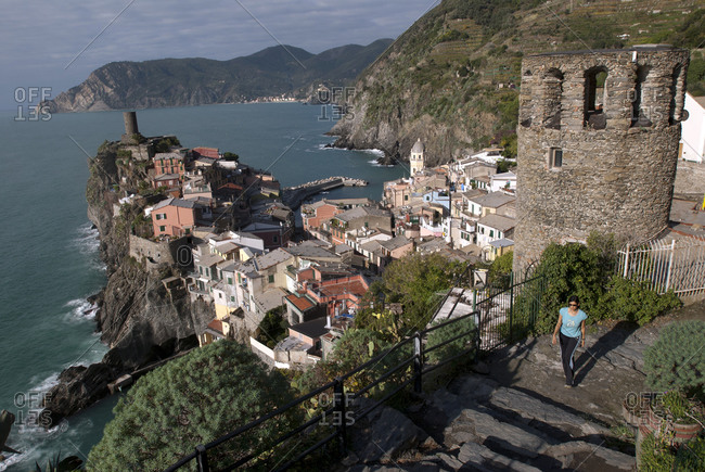 Woman walking along a seaside trail in Vernazza, Italy in the Cinque Terre region