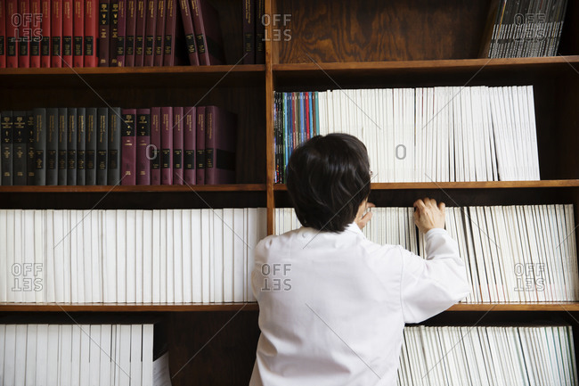 Scientist selecting book from shelf