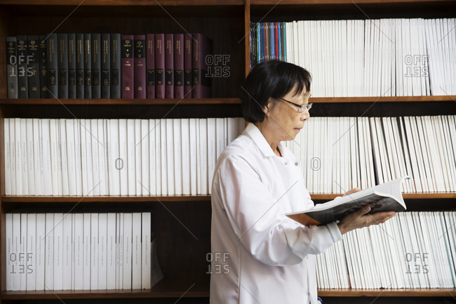 Scientist reading journal by book shelf