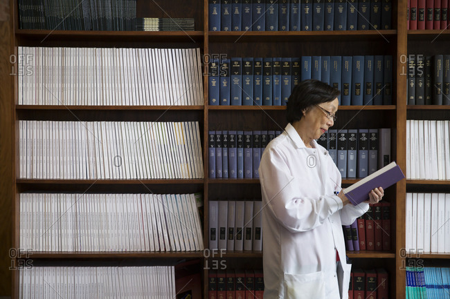 Scientist reading textbook by bookshelf