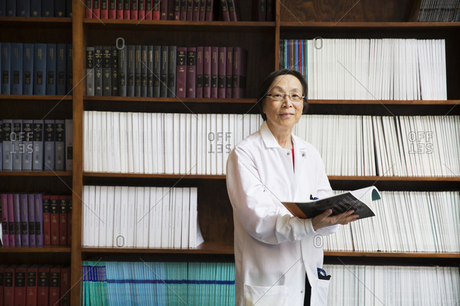 Scientist with book by bookshelf