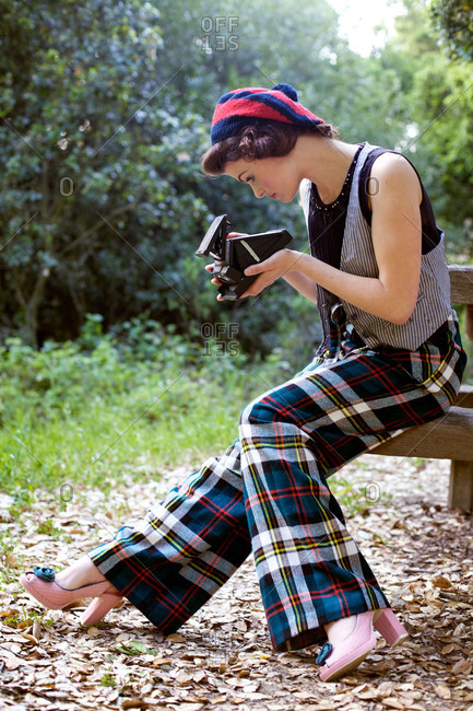 Stylish woman in plaid pants taking photo in park
