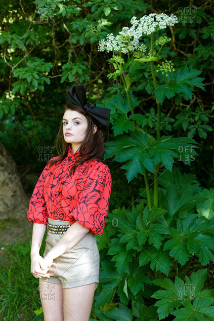 Stylish woman standing by bushes in park