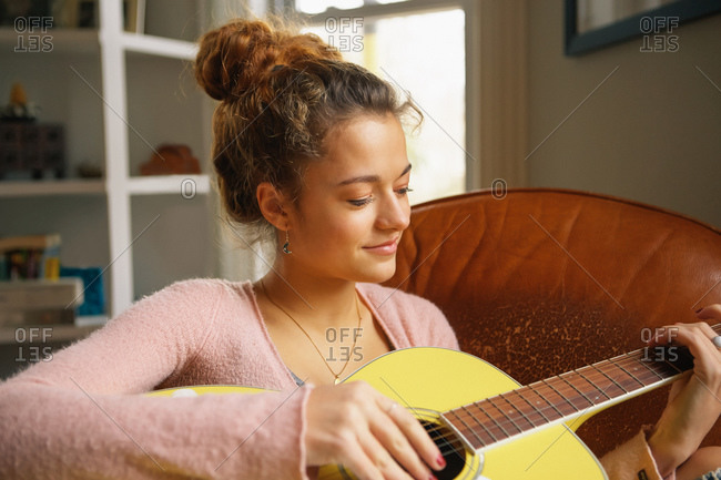A teenager plays a guitar in her living room