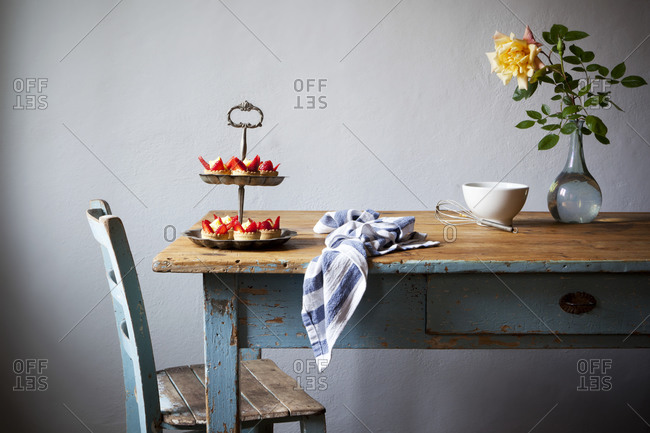 Cream and strawberry pastries on a cake stand in a rustic kitchen