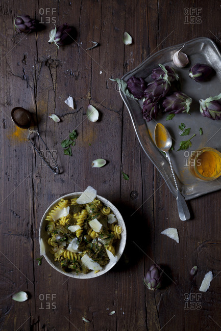 Bowl of pasta with artichokes and turmeric on a table with other ingredients