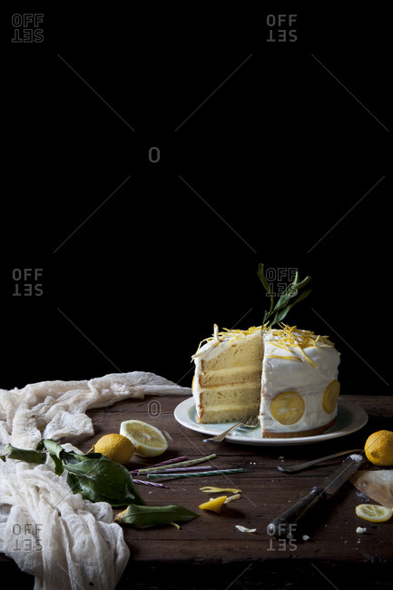 A sliced frosted lemon cake with candied lemon slices on a rustic table