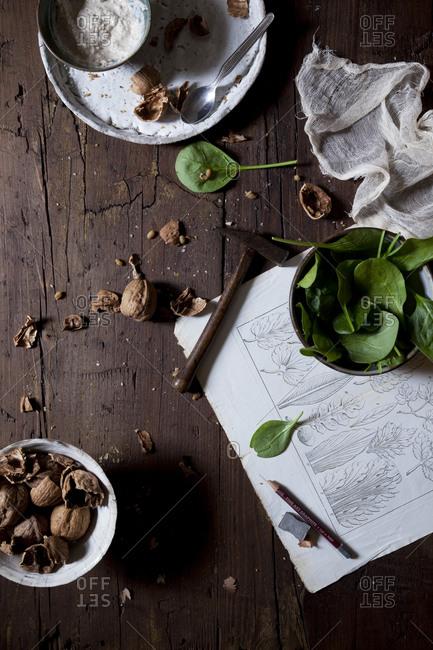 Fresh spinach salad with a bowl of yogurt walnut dressing on a wooden table
