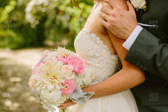 Bride and groom in embrace outdoors