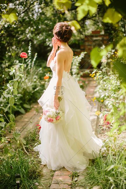 Bride standing in overgrown garden