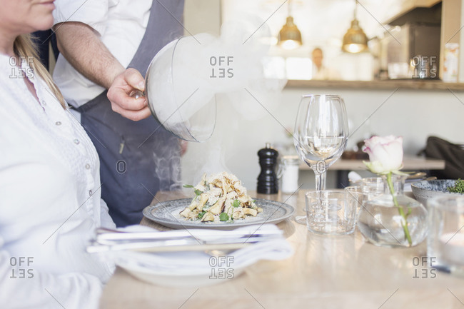 Waiter presenting a delicacy for a guest