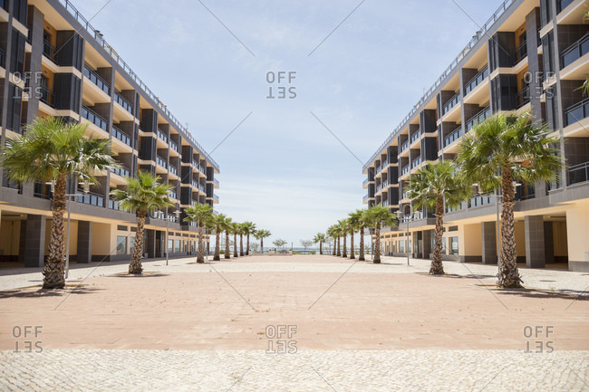 Two apartment buildings with palms in front