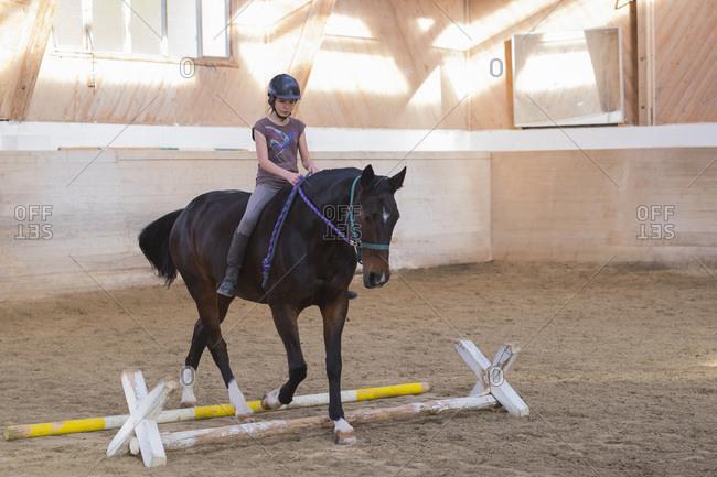 Teenage girl riding horse at riding ring