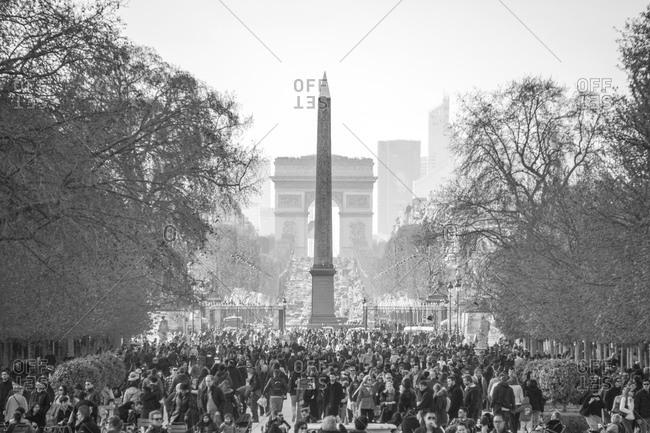 Paris, France - April 6, 2015: View to obelisk and Arc de Triomphe with crowd