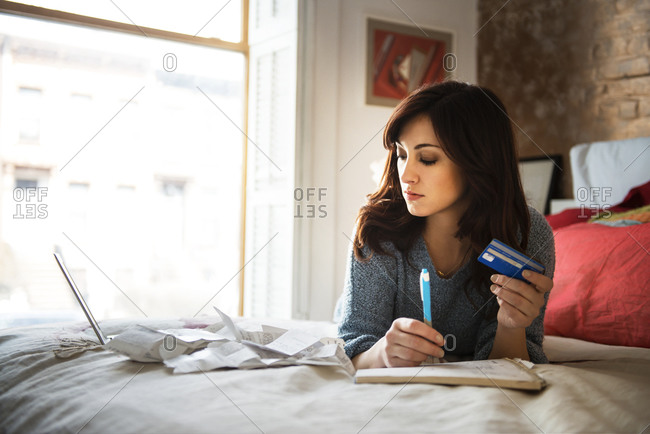 Woman on bed with credit card and bills