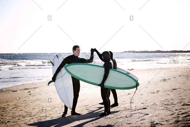 Three surfers high five before heading into the water