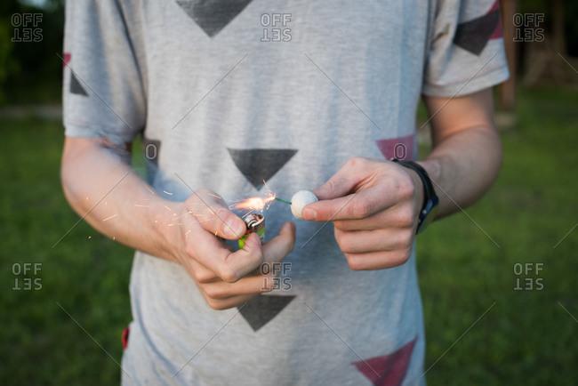 A young man lighting a smoke bomb