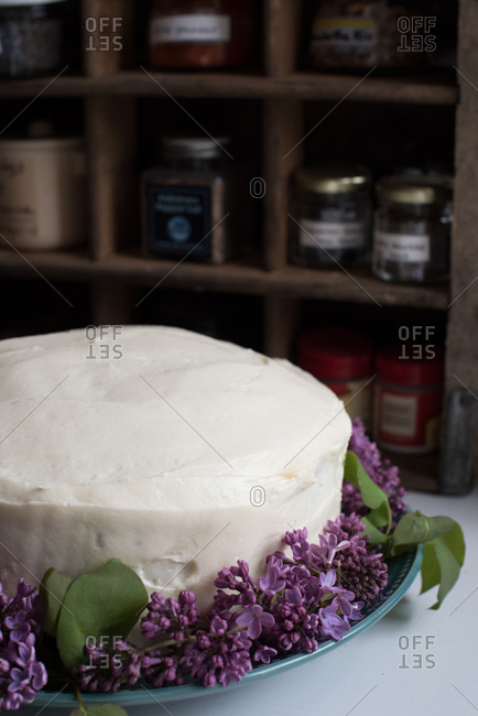 Homemade cake with vanilla icing and lilac decorations