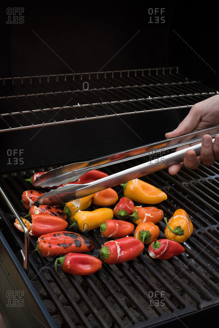 A man turning stuffed hot peppers on a grill