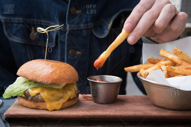 A man dipping a french fry into ketchup next to cheeseburger