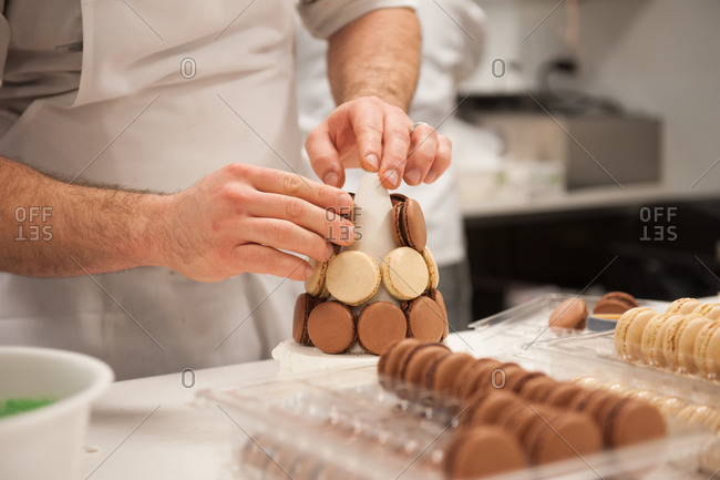 A chef building a display of macarons